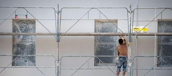 Photo peintre en bâtiment sur échafaudage extérieur